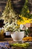 Hierbas, bayas y flores con el mortero, en backgrou de madera de la tabla Foto de archivo