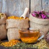 Hierbas curativas en bolsos de la arpillera y taza de té sana Foto de archivo libre de regalías