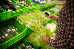 Hierbas de compra del cliente irreconocible en supermercado fotos de archivo