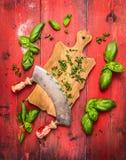 Hierbas de la albahaca que tajan en tabla de cortar con el cuchillo remilgado viejo, fondo de madera rojo Imagen de archivo