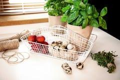 Hierbas de la cesta de la cocina con los huevos Fotografía de archivo