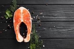 Hierbas de la pimienta y de la sal del filete de color salmón en la tabla negra imagen de archivo