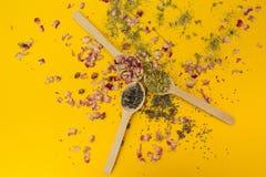 Hierbas secadas en una cuchara de madera en un fondo amarillo imagen de archivo libre de regalías