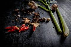 Hierbas y especias alrededor de la tabla de cortar vacía en backgr de piedra oscuro Fotografía de archivo