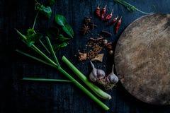 Hierbas y especias alrededor de la tabla de cortar vacía en backgr de piedra oscuro Imagen de archivo