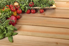Hierbas y verduras en un tablero de madera en blanco Foto de archivo