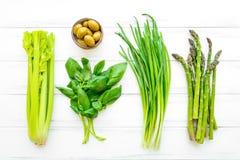 Hierbas y verduras frescas verdes en el fondo de madera blanco Endecha plana, fondo del vegano del eco imagen de archivo