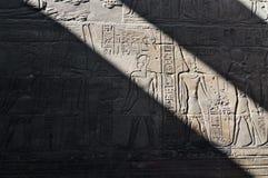Hieroglyfer som maskeras i ljus i skugga på den Luxor templet Arkivbild