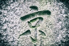 The hieroglyph cut in the stone. The cut of an Asian hieroglyph in the rough stone stock photo