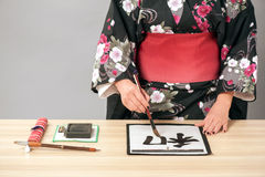 Hieroglyph of Traditional Japanese or Chinese. Woman in kimono writing. Closeup of a Japanese or Chinese woman writing hieroglyph in a traditional way with ink Stock Photos