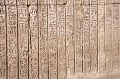 Hieroglyphics from Kom Ombo, Egypt. Hieroglyphics next to the relief of Khonsu, Hathor and Sobek his father. Kom Ombo, Egypt Royalty Free Stock Photo