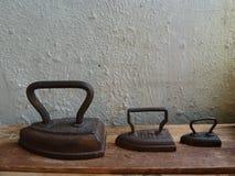 Hierro de tres vintages en un tablero de madera foto de archivo libre de regalías