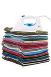 Hierro encima de las camisas plegables en una pila Fotos de archivo libres de regalías