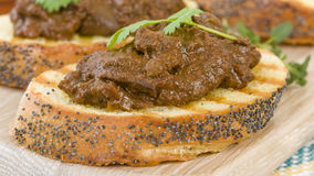 Higados de Pollo. Chicken livers with chorizo & spring onions finished with a dark Cajun tomato sauce on top of crusty bread Royalty Free Stock Images