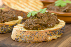 Higados de Pollo. Chicken livers with chorizo & spring onions finished with a dark Cajun tomato sauce on top of crusty bread Royalty Free Stock Photo