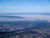 High above city. Aerial view of a city lying far below, some clouds in the sky stock photography