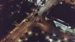 Aerial, Cars Traveling Around City Streets. High above city streets, illuminated streets and buildings light up at night stock video footage