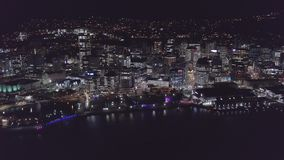 Aerial Rise, City Skyline At Night Beautiful Lights. High above city streets, illuminated streets and buildings light up at night stock footage
