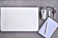 High above view of office workplace with laptop and mouse with paper, pen ,eyeglasses, usb stick, watch on grey desk Royalty Free Stock Images