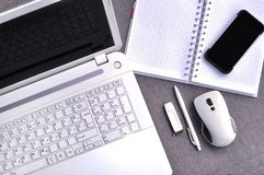 High above view of office workplace with mobile phone and laptop close up computer keyboard and mouse with notebook, pen and usb. Flash on grey desk. Working Royalty Free Stock Images