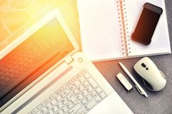 High above view of office workplace with mobile phone and laptop close up computer keyboard and mouse with notebook, pen and usb Royalty Free Stock Photography