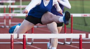 High school girls racing the hurdles outdoors. High achool girls running in a hurdle race outside during a spring track snd field race royalty free stock photos