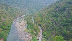 High aerial view rocky river and road between tropical forests. High aerial panoramic view long mountain rocky river runs near road meandering between tropical stock video footage