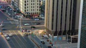 High aerial time lapse view of cars on a traffic light and crowds of people crossing a street in the city stock video