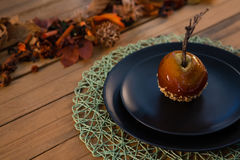 High angle view of caramelized apple served in plate. High agnle view of caramelized apple served in plate on wooden table Stock Photography