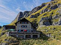 High alpine chalet in mountain landscape. The chalet Bad Kissinger Hütte at mount Aggenstein, Austria. A place to rest by mountain hiking. People sitting Royalty Free Stock Images