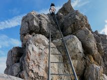High-alpine ladder in the mountains and hiker on top royalty free stock photos