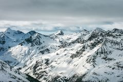 High Alpine landscape. Snow-capped mountain peaks and beautiful. Tops. High grey clouds Stock Image