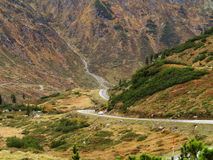 Mountain pass road in martian-like scenery with BMW car Royalty Free Stock Image