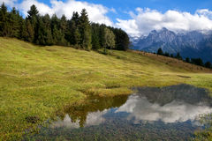 High Alps and blue sky reflected in wild lake Royalty Free Stock Photography