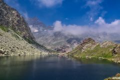 Lake Fiorenza in Alps, Italy. High in the Alps, Italy in the summer. The water reflections in Lake Fiorenza.nHuge rocks. Blue sky with fluffy clouds.n royalty free stock photography