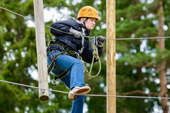 High altitude adventure. Teenage female in high altitude adventure. Fearless and brave she climbs and swings through the canopy in safty gear and harness Royalty Free Stock Images