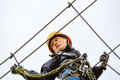 High altitude adventure. Teenage female in high altitude adventure. Fearless and brave she climbs and swings through the canopy in safty gear and harness stock photos