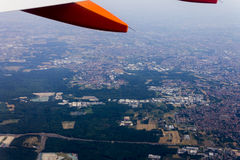A high altitude aerial shot of flat landscape with fields, forests and cities and a white and orange wing Stock Image