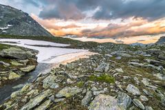 High altitude alpine lake and cloudscape at sunset Stock Photo