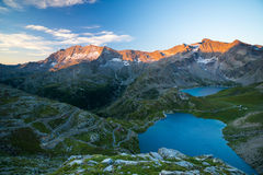 High altitude alpine lake, dams and water basins in idyllic land with majestic rocky mountain peaks glowing at sunset. Wide angle Stock Photos