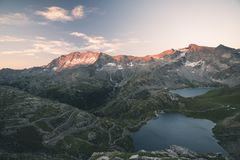 High altitude alpine lake, dams and water basins in idyllic land with majestic rocky mountain peaks glowing at sunset. Wide angle Stock Photo
