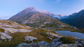 High altitude alpine lake in idyllic land with majestic rocky mountain peaks. Long exposure at dusk. Wide angle view on the Alps. High altitude alpine lake in royalty free stock image
