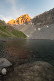 High altitude alpine lake in idyllic land once covered by glaciers. Majestic rocky mountain peak glowing at sunset. Wide angle ver Stock Photography