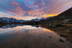 High altitude alpine lake, reflections at sunset Royalty Free Stock Image