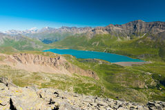 High altitude blue lake, dam on the Italian French Alps. Expansive view from above, clear blue sky. High altitude blue lake, dam on the Italian French Alps Royalty Free Stock Images