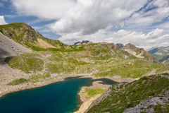 High altitude blue lake in idyllic uncontaminated environment once covered by glaciers. Summer adventures and exploration on the I Royalty Free Stock Photos