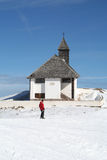 High altitude Church. Church in Hahnenkamm, above Kitzbuhel in Austria, with a skier in front royalty free stock photos
