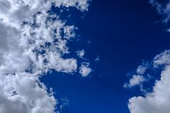 High-altitude clouds seen during the summer, against a blue background, prior to a storm. Gathering storm clouds can be seen in this view of a summer sky. The Royalty Free Stock Images