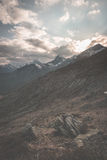 High altitude extreme terrain, rocky mountain peak and jagged ridge, with scenic dramatic stormy sky. Wide angle view in backlight Stock Photography