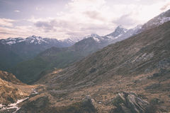 High altitude extreme terrain, rocky mountain peak and jagged ridge, with scenic dramatic stormy sky. Wide angle view in backlight Royalty Free Stock Photo
